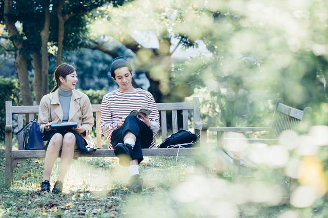 公園で腰掛けるカップル