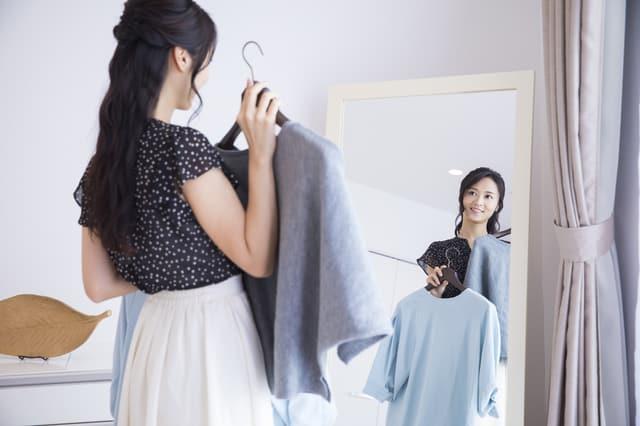 鏡の前でコーディネートする女性